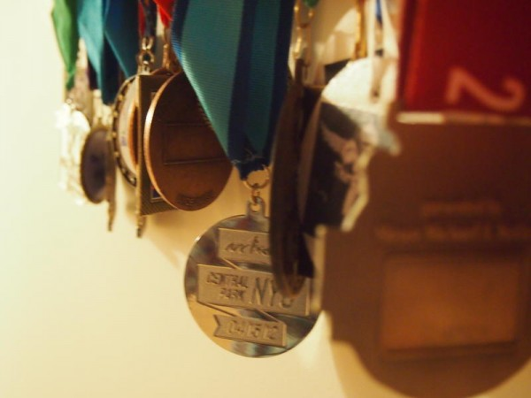 Medals from numerous races hang on Michele Flynn's &quotRace Bling&quot rack at her home in Cape Elizabeth.