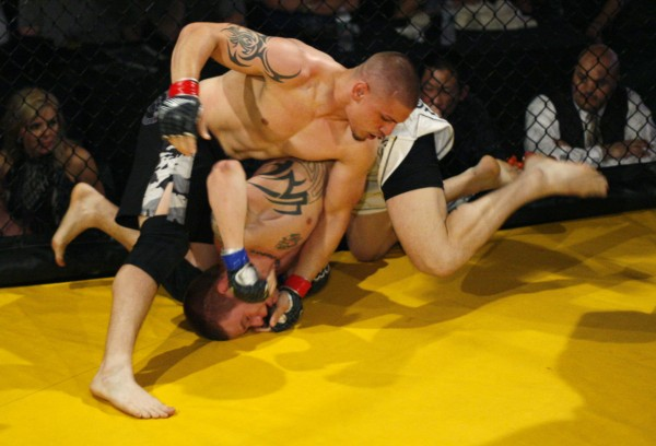 Anthony Kaponis of AFT/Galdiator (top) punches Ryan Sanders, of Youngs MMA, during the Maine Event in April 2011 at the Stevens Avenue Armory in Portland. Sanders will fight for the New England Fights Maine MMA welterweight (170-pound limit) title on Sept. 8 in Lewiston.