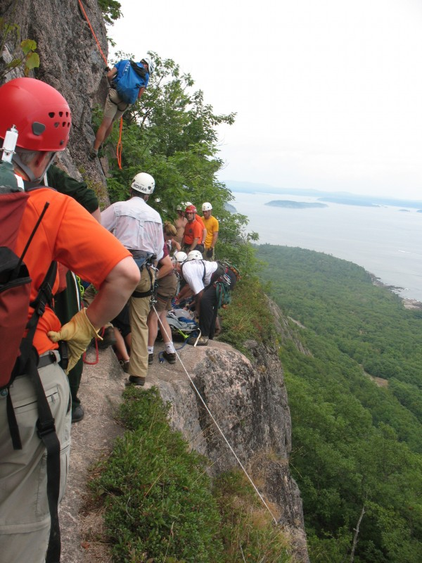 Rescuers work Saturday to carry a 22-year-old woman to the top of Champlain Mountain after she fell while hiking the Precipice Trail. She was taken by helicopter to Eastern Maine Medical Center in Bangor, where she later died.