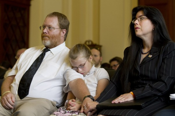 Ruth Moore of Milbridge, Maine, who was raped twice while serving in the Navy, holds hands with her husband, Butch Moore, with daughter Samantha Moore before testifying before the Veterans Affairs subcommittee on Disability Assistance and Memorial Affairs on Wednesday.