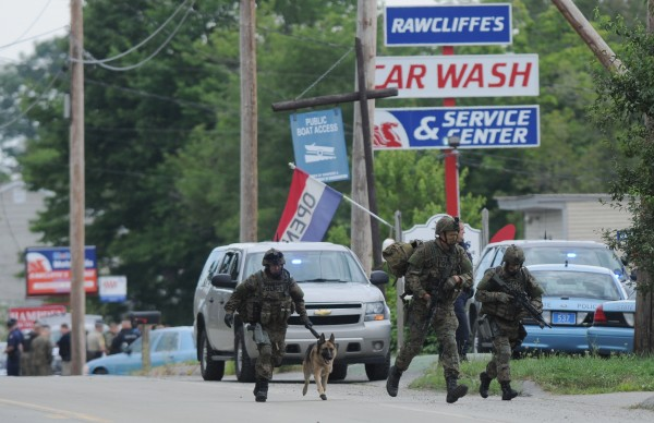 Maine State Police tactical team members maneuver into place along Main Road North in Hampden Friday, July 27, 2012.