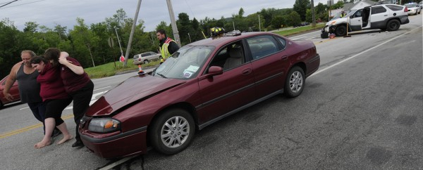 Robert Seekins, 52, of Monroe (left) helps his 17-year-old daughter who injured her foot from one of the vehicles involved in the two-vehicle accident that slowed traffic near the corner of Route 46 and Route 1A in Holden on Thursday morning, July 26, 2012. The girl's mother (right) drove her to the hospital. No serious injuries were reported.