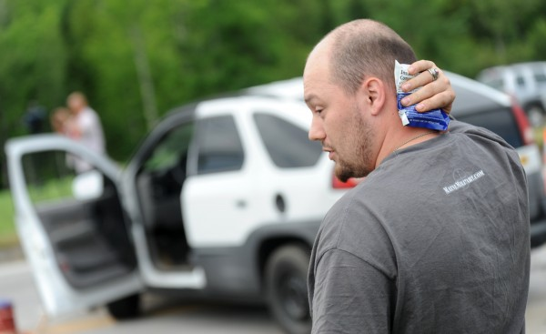 Jayson LaPoint of Bucksport holds a cold pack to his neck as he stands near his vehicle as fire and rescue attend to the occupants of the other vehicle that collided with his at the corner of Route 46 and Route 1A in Holden on Thursday, July 26, 2012.