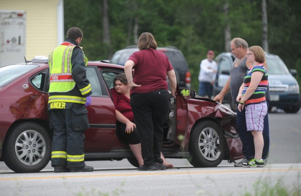 Public safety personnel talk with occupants of one of the vehicles involved in a two-vehicle accident, including the driver, Robert Seekins, 52 of Monroe (right) and his 17-year-old daughter (seated) that slowed traffic near the corner of Route 46 and Route 1A in Holden on Thursday morning, July 26, 2012.