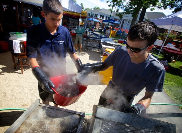 Thomas Robichaud fills Jack Amoroso's bucket with steamers at the 47th annual Yarmouth Clam Festival on Friday, July 20, 2012.