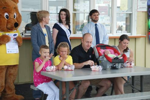 Special guests at the launch of the TAMC Centennial ice cream dish get the first taste after the announcement was made on Friday, July 20, 2012. Participating in the inaugural test tasting are (front, from left to right) 9-year-old Hadley McClean of Presque Isle; 6-year-old Kylie Pelletier of Frenchville; Adam Richardson, 3-week-old Aiva Richardson, and Lisa Plourde of Caribou. Waiting for their taste of the concoction in a waffle cone are (back, same order) TAMC Teddy, TAMC President and CEO Sylvia Getman, Miss Maine 2012 Molly Bouchard of Caribou, and Matthew Lincoln of Houlton Farms Dairy. The custom ice cream dish goes on sale on Aug. 1 and will help the hospital celebrate its 100th birthday and also raise money for needed pediatric equipment.
