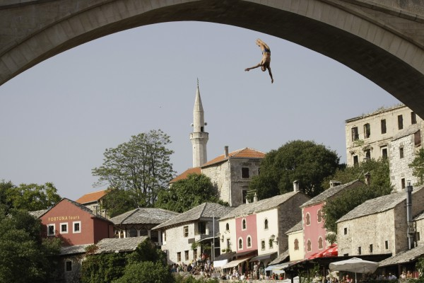 A diver drops from the Old Mostar Bridge during 446th traditional annual high diving competition in Mostar, south of the Bosnian capital of Sarajevo, on Sunday, July 29, 2012. A total of 49 divers from Bosnia and neighboring countries competed, diving  from the 25 meters-high Old Mostar Bridge into the Neretva river.