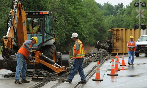 Maine Department of Transportation wokers and Pan Am Railroad workers clear damaged pavement from the traffic lane near the intersection of Kenny Lane and Route 15 in Bucksport on Sunday, July 29, 2012, after a train carrying paper products overturned.