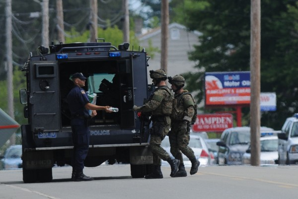 A Maine State Police officer hands a tactical team member water during their police action off Main Road North on Friday, July 27, 2012. A person was shot on the Marina Road and a standoff was under way Friday morning, Hampden police Officer Dan Stewart confirmed Friday morning. Ed David, the state