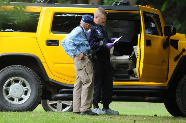 Maine Deputy Chief Medical Examiner Dr. Ed David (left) and State Police Detective Micah Perkins examine a piece of paper while standing next to a vehicle in the yard of 10 Marina Road in Hampden while investigating a murder-suicide at that adress on Friday, July 27, 2012.