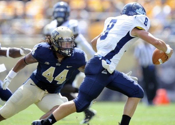 Maine quarterback Warren Smith (8) gets away from Pittsburgh linebacker Shane Gordon (44) during a game last season in Pittsburgh. Maine has added two contests against BCS opponents in 2013.