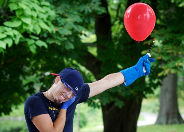 Zachary Chopchinski, vice president of the University of Southern Maine Chemistry Club, waits for the boom as he lights a balloon filled with oxygen and hydrogen during a science show for children in Portland's Deering Oaks Park on Thursday, July 26, 2012.