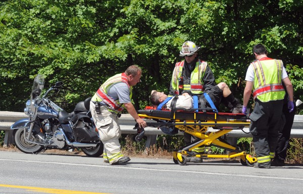 The driver of a Harley-Davidson motorcycle is taken to the nearby ambulance after first responders lifted him over the guardrail, onto Route 1A in Holden on Thursday, July 19, 2012. Holden Police Chief Gene Worcester said it appears the driver of the motorcycle had to &quotlay down&quot his bike to avoid cars stopped to turn left in the front of him. The driver was transported to the hospital with injuries that were not life threatening. Units from Holden and Brewer responded to the accident.