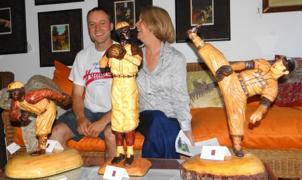Jon Moro sits on a couch with Leslie Curtis, owner of Leslie Curtis Designs, a Camden furnishings and crafts store. Displayed on the coffee table are wood carvings of Negro League baseball players created by Moro.