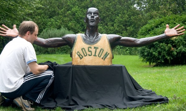 Rockport sculptor Jon Moro sits with his latest piece, a life-sized rendering of Boston Celtics star Kevin Garnett.