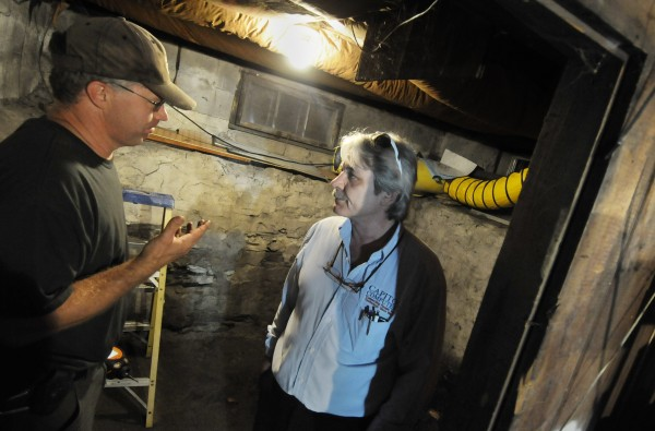 John Selleck (left), an oil, materials and hazards responder with the Maine Department of Environmental Protection, answers question regarding cleanup from Forrest Mulheron III after a tanker truck removing unused heating oil from his home's basement heating oil tank overflowed, causing spillage in the family's yard and basement off French Street in Bangor on Tuesday, July 25, 2012. Behind them is a yellow ventilation hose, attached to a fan had been installed to help remove the noxious oil fumes from the basement.