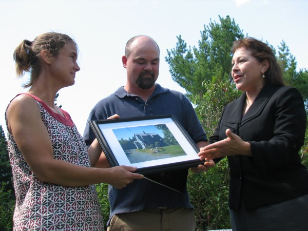 Bar Harbor residents Jen Harry and John Barnes hold a framed photograph of their new house on Wednesday, July 25, 2012, while speaking with Tammye Trevino of USDA Rural Development. Trevino and other federal, state and banking officials held a press conference at the couple's home on Crooked Road to highlight programs that are available to first-time homebuyers in Maine.