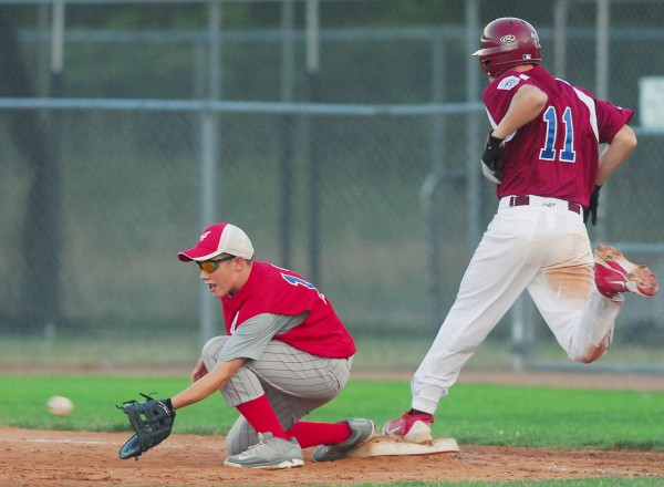 Bangor's Goodine Tanner beats the throw to Acadians first baseman Aaron Snurkowski for an infield hit during fifth-inning action during the state Junior League championship at Mansfield Stadium in Bangor on Tuesday, July 24, 2012. Bangor won 11-0.