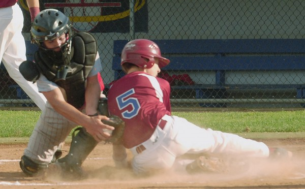 Bangor's Nick Moore (5) slides safely at home plate ahead of the tag from Acadians' catcher Dylan Collin (6) in first-inning action of the state Junior League championship at Mansfield Stadium in Bangor on Tuesday, July 24, 2012.