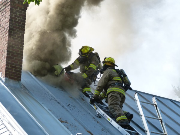 Firefighters use a power saw to cut through the metal roof of a two-story farmhouse at 246 Coombs Road in Brunswick to vent the smoke.