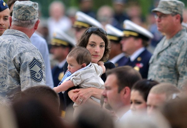 Jenny Ellerbe carries her 6-month-old son Rob during a memorial service for her husband Ryan David and three other North Carolina Air National Guard airmen in Charlotte, N.C., on Tuesday, July 10, 2012. Lt. Col. Paul Mikeal, Maj. Joseph McCormick, Maj. Ryan David and Senior Master Sgt. Robert Cannon all died July 1 when their C-130 crashed while fighting a wildfire in the South Dakota Black Hills. Two crewmen were injured.