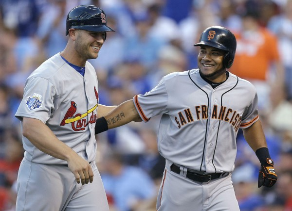 The National League's Melky Cabrera, right, of the San Francisco Giants, celebrates his two-run home run with Matt Holliday, of the St. Louis Cardinals, during the fourth inning of the MLB All-Star baseball game, Tuesday, July 10, 2012, in Kansas City, Mo.