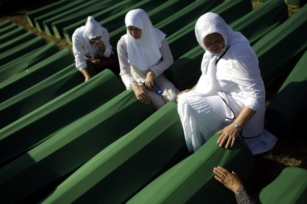 Women sit next to coffins of their relatives at the Potocari memorial complex near Srebrenica, some 160 kilometers east of Sarajevo, Bosnia and Herzegovina on Wednesday, July 11, 2012. Thousands gathered at the Potocari memorial complex on Wednesday for the mass burial of 520 bodies, marking the 17th anniversary of the Srebrenica massacre.