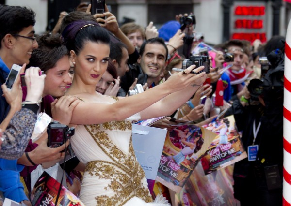 U.S singer Katy Perry takes a photo with her fans as she arrives on the red carpet at a central London cinema for the European Premiere of her film &quotPart of Me,&quot Tuesday, July 3, 2012.