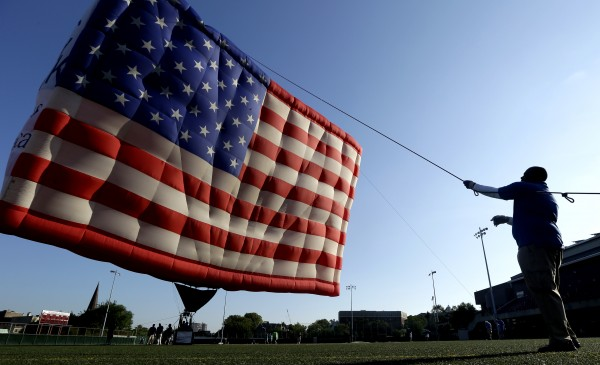 Wayne Matthew holds a rope as he helps a crew raising a hot air balloon shaped like the U.S. flag at Stevens Institute of Technology in Hoboken, N.J. on Tuesday, July 3, 2012.