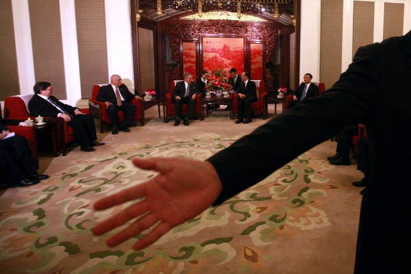 A Chinese security guard motions journalists to leave after a photo call with Cuban President Raul Castro (center at left) and Chinese Premier Wen Jiabao (center at right) during a meeting held at the Zhongnanhai diplomatic compound in Beijing on Friday, July 6, 2012. The trip is Castro's first to China since taking over from his brother in 2008.