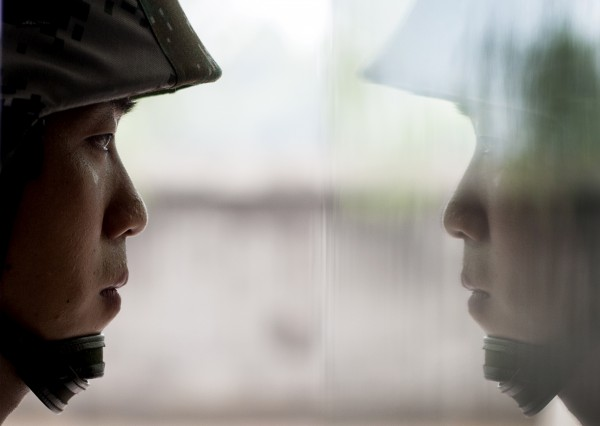 A Chinese soldier is reflected on a window glass as he stands guard during a media oppotunity for the coverage of China's attack helicopter Z-9WZ at a Chinese Liberation Army base, ahead of Army Day on Aug. 1, on the outskirts of Beijing on Tuesday, July 24, 2012.