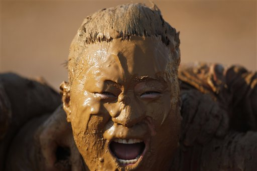 A competitor celebrates his team's victory of a swamp football match in a man-made mud pool in Beijing, China on Sunday, July 15, 2012. The sports, which originated from England, is usually played in a bog or swamp and in the Beijing games, the rules require at least one female competitor in each team.
