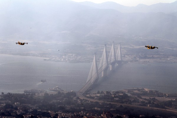Aircrafts fly over the western Greek port city of Patras as the bridge of Rio-Antirion bridge is seen in the background during a wildfire on Wednesday, July 18, 2012. Greek authorities declared a state of emergency near the country's third-largest city Wednesday due to raging wildfires, but officials said no inhabited areas were under immediate threat.
