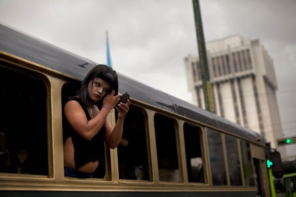 A transgender person puts make-up on while riding in a bus on his way to a gay pride parade in Guatemala City on Saturday, June 30, 2012.