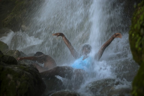 Pilgrims bathe in a waterfall believed to have purifying powers in Saut d' Eau, Haiti on Saturday, July 14, 2012. The annual pilgrimage is made in honor of Haiti's most celebrated patron saint, Our Lady of Mount Carmel. Legend has it that she appeared on a palm tree in 1847 in the Palms Grove in Saut d'Eau and was integrated into Haiti's voodoo culture as the goddess of love, Ezili Danto.