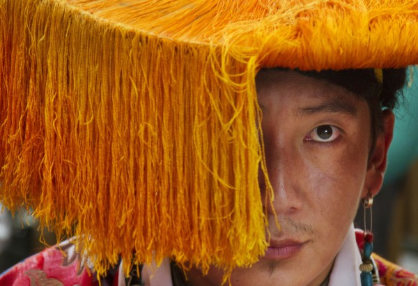An exiled Tibetan in traditional costume waits to perform a dance at Tsuglakhang temple in Dharmsala, India on Friday, July 6, 2012. The Dalai Lama celebrates his 77th birthday with festivities held for the entire day at the temple complex.