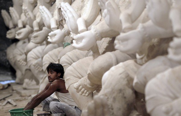 An Indian worker prepares idols of elephant-headed Hindu god Ganesh at a workshop in Mumbai, India on Tuesday, July 17, 2012. The idols will be immersed in the Arabian Sea at the end of a festival.