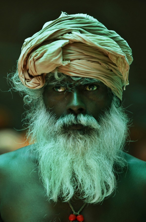 A Hindu holy man looks on as he waits under the roof of a green sheet to register for the annual pilgrimage to the Amarnath cave shrine in Jammu, India, Tuesday, July 3, 2012. Hundreds of thousands of pilgrims flock each year to the Amarnath shrine which contains a large icicle revered by Hindus as an incarnation of Lord Shiva, the Hindu god of destruction and regeneration.