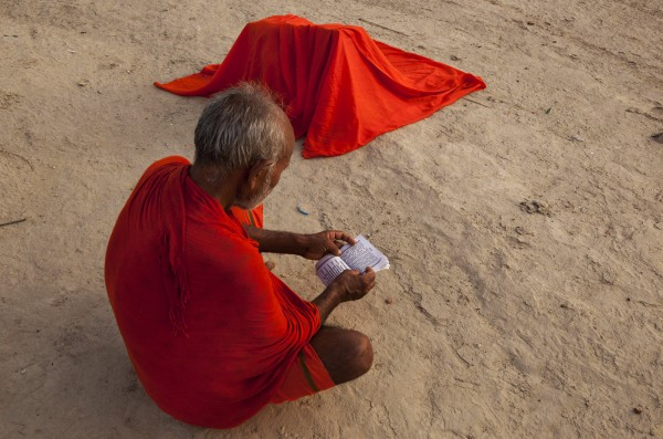 A Hindu devotee reads a holy book near his belongings covered with a piece of cloth to dry after bathing at Sangam in Allahabad, India on Sunday, July 1, 2012. Sangam, the confluence of the rivers Ganges and Yamuna, is one of Hinduism's important centers.