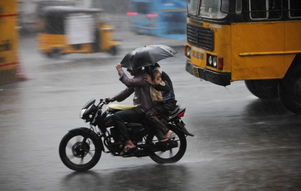 An Indian family on a motorcycle protect themselves with an umbrella from a heavy monsoon shower in Hyderabad, India on Tuesday, July 17, 2012. The monsoon rains which usually hit India from June to September are crucial for farmers whose crops feed hundreds of millions of people.