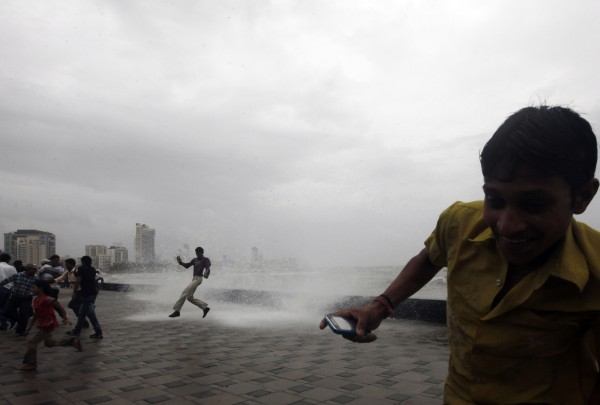 People enjoy a high tide at the Arabian Sea coast after monsoon rains in Mumbai, India on Tuesday, July 24, 2012. Indians have been desperately waiting for the long-delayed deluge of this year's monsoon, the annual rains that replenish India's rivers and quench crops to keep this vast, agricultural nation of 1.2 billion fed through the year. So far, the rains were at least 22 percent below normal, several states faced drought and farmers feared grave losses. Some analysts put the rain deficit at 31 percent.