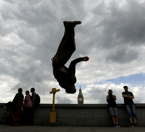 Street performer Oliver Presman does a flip for tourists, with Big Ben visible across the River Thames, Saturday, July 21, 2012, in London. Opening ceremonies for the 2012 London Olympic Games are scheduled for Friday, July 27.