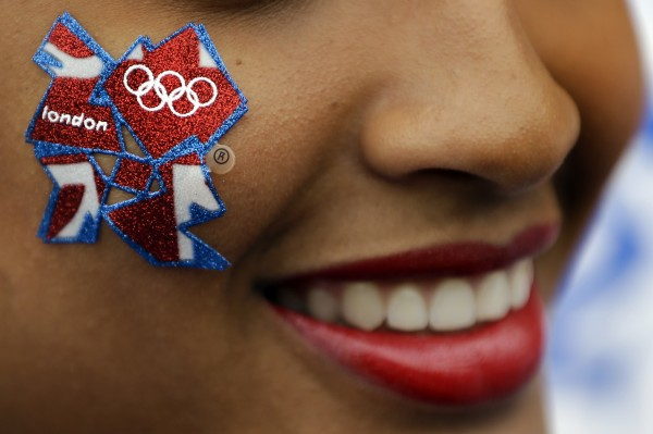 A young woman wears a London Olympics logo on her cheek outside the Olympic Park ahead of the 2012 Summer Olympics Opening Ceremony on Friday, July 27, 2012, in London.