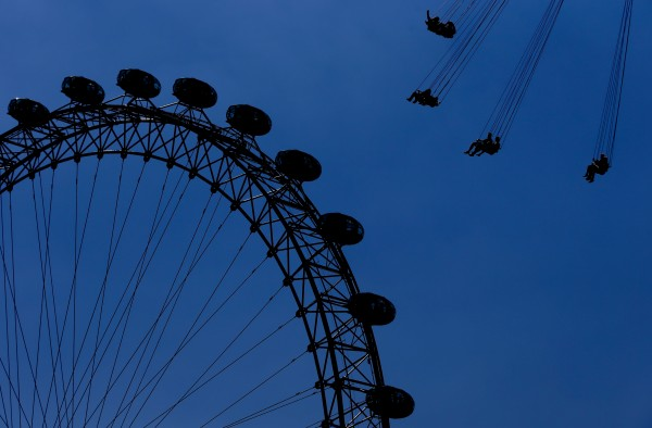 Visitors ride a large carousel next to the London Eye (left) on the south bank of the river Thames in London on Tuesday, July 24, 2012. The city will host the 2012 London Olympics with opening ceremonies for the games scheduled for Friday, July 27.