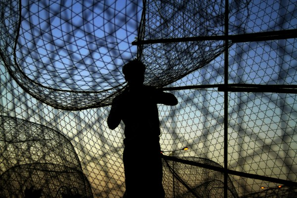 A fisherman works on fish traps at sunset in Malkiya Village, Bahrain, on the Persian Gulf coast on Tuesday, July 10, 2012.