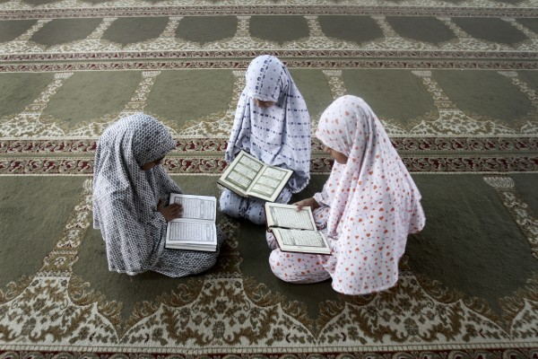 Palestinian girls read verses from the Quran, Islam's holy book, at a mosque as part of their activities in a summer camp dedicated to the preservation of the Quran in Gaza City on Tuesday, July 10, 2012. About 13,000 students, both male and female participate in similar summer camps throughout Gaza Strip.