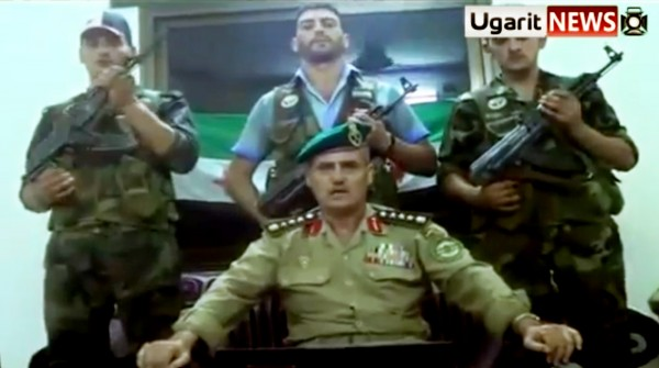 This Saturday, July 21, 2012 image made from amateur video released by the Ugarit News and accessed Sunday, July 22, 2012, purports to show Syrian Brig. Gen. Abdul-Nasser Farzat, center front,  from the Aleppo Academy for Military Engineering, and warrant officer Ziad Ahmad Khodr from Criminal Security, center back, announcing their defection to the Free Syrian Army in Aleppo, Syria. In the video Farzat says, &quotI have joined the Free Syrian Army, the army of heroes that is defending the nation.&quot