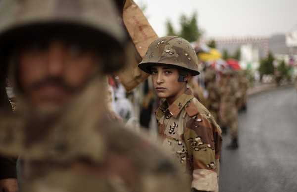 A young Yemeni soldier (center) stands guard as protestors demanding that the relatives of former President Ali Abdullah Saleh be fired from army and police posts demonstrate in Sanaa, Yemen on Friday, July 27, 2012.