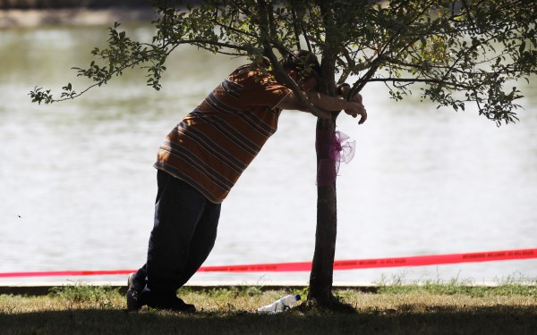 Dan Morrissey leans on a tree near Meyers Lake where his daughter Lyric Cook-Morrissey, 10, and Elizabeth Collins, 8, disappeared last Friday, Tuesday, July 17, 2012, in Evansdale, Iowa. The girls' bikes were found Friday afternoon near a bike trail at the edge of the lake.