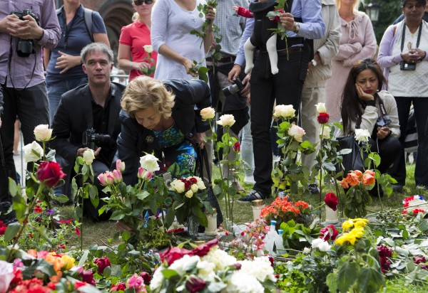 People lay down flowers outside the cathedral in Oslo, Norway Sunday July 22, 2012, on the first anniversary of a bombing and shooting rampage in Oslo and on Utoya Island.  Norway on Sunday paused to commemorate the 77 victims of a bomb and gun massacre that shocked the peaceful nation one year ago, a tragedy that the prime minister said had brought Norwegians together in defense of democracy and tolerance.
